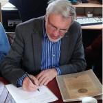 Thijs van Oord tekent het formulier waarmee de overdracht van de collectie officieel is.
